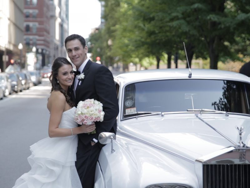 Bride and groom with white Rolls-Royce limo in Boston